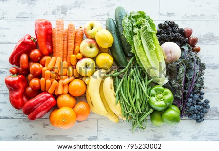 A tabletop arrangement of a variety of fresh fruits and vegetables sorted by colors