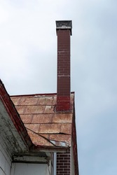 A tall brick chimney on a metal roof