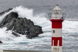 A tall circular lighthouse tower has horizontal red and white colors against a stormy sea. The lighthouse has steps, windows, a walkway, and metal walls. The building sits high on top of a rocky cliff