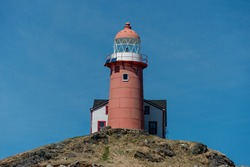 A tall circular red and white lighthouse with an attached light keeper's house. The sky is very dramatic with lots of white clouds and blue sky underneath.  There's grass in front of the lighthouse.