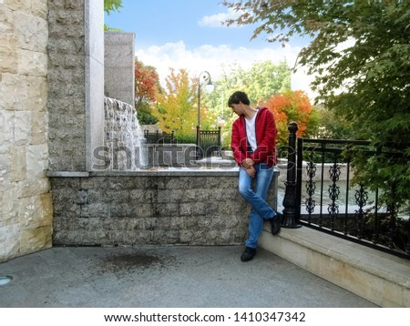 A tall dark-haired man stands and looks into the pool of a cascade fountain in Heydar Aliyev Park in Kiev. A man leans on a stone wall near an artificial waterfall on an autumn sunny day
