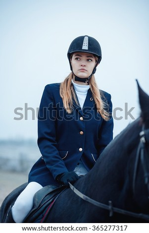 a tall girl with long blond hair in a jockey outfit with a beautiful black horse in an empty snow-covered field in winter #365277317