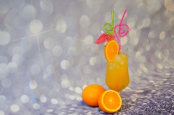 A tall glass of orange juice with ice, decorated with a slice of citrus, straws and an umbrella stands on a gray abstract background next to fruits. Close-up.