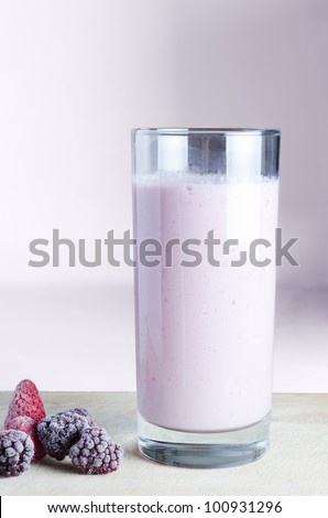 A tall glass of pink smoothie on a wooden chopping board with frozen summer fruits, against a pink background.  This is a vegan and dairy-free smoothie made with soya milk.