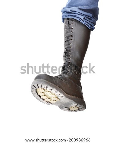 A tall lace-up combat boot stomping with the sole visible