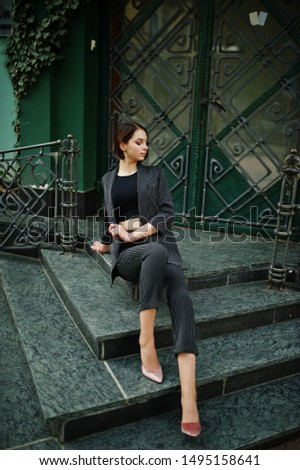 A tall leggy young beautiful and elegant model woman at formal wear posed on stairs.
