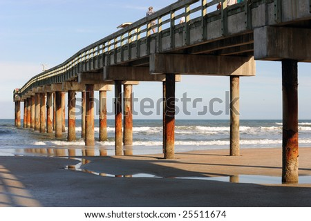 A tall pier taken in the late afternoon sunlight showing long, deep shadows.