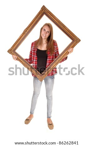 A tall pretty woman holding a picture frame for her upper body, in jeans and a checkered shirt, over white.