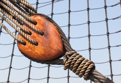 a tall ship detail showing 19th century wooden block and tackle with hemp rope for sail adjustment