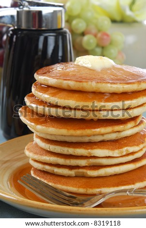 A tall stack of pancakes covered in syrup and butter