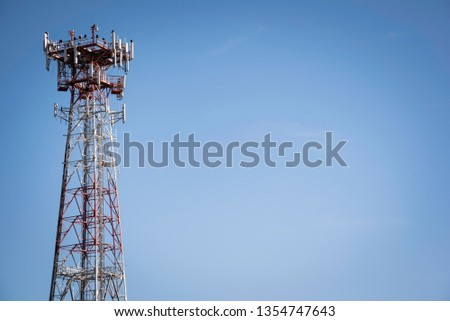 A tall stand-alone cellular and telecommunications tower set against a clear blue sky.