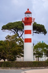 A tall, white and red lighthouse, is located in the picturesque port city of La Rochelle in France. The lighthouse is surrounded by trees and green space, located in an area frequented by tourists.