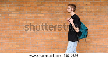 A tall white Caucasian young adult teenage male walks in front of a brick wall. Lots of room for your copyspace text. He has a backpack and glasses