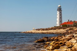 A tall white lighthouse stands on a rocky seashore