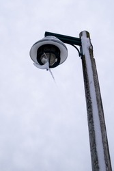 A tall wooden street light pole with a round light fixture at the top of the structure. The exterior bulb has an odd shape of snow and ice hanging off the lamp.