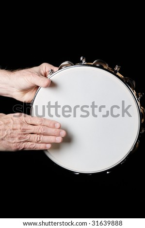 A tambourine being played by hands isolated against a black background in the vertical format.