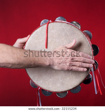 A tambourine being played isolated against a red background in the square format with copy space.