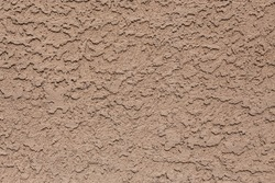 A tan colored abstract stucco background.