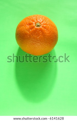 A tangerine on a green background.