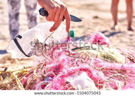 A tangled mess of fishing nets plastic rope and other debris washed up on a coastal beach. Save the Planet stock picture.