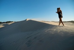 A tanned blonde model in a black play suit walks across the peak of a sand dune