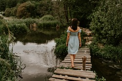 A tanned brunette girl in a turquoise dress with white polka dots walks across the river alone an old wooden bridge. Against background of dark green trees. cloudy weather. back view. Woman at nature