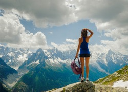 A tanned girl with long legs stands on top and looks at the snow mountains