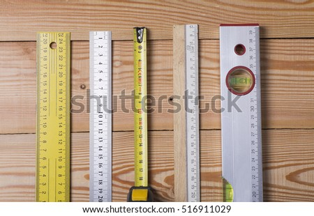 A tape measure, ruler, construction level. Various measuring tools on wooden background