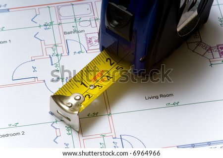 A tape measure slightly open lying on top of a house floor plan, construction industry or real esate