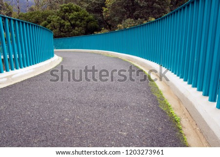 A tarmac path curving away, framed by blue metal railings with trees in the background #1203273961