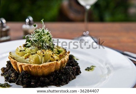 A tart made of cauliflower in a pastry shell, on a bed of mushrooms and herbs. - stock photo