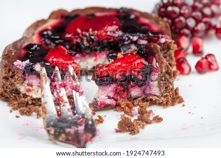 a tartlet broken during a meal, a tartlet with berry filling is broken and crumble , a round tartlet with strawberries and blueberries in curd cream during dessert