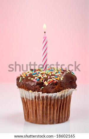 A tasty muffin chocolate with candle isolated on color background. Flame at focus and shallow depth of field