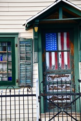 A tattered American flag hangs inside a door window
