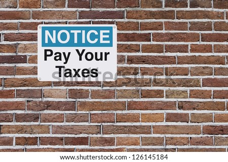 A tax reminder mounted on a brick wall with copy space