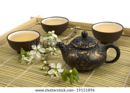 A tea serving in brown ceramic cups and teapot .
