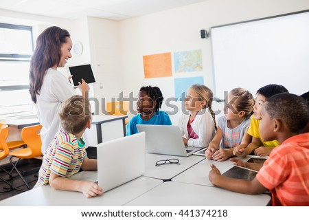 A teacher giving lesson with technology in classroom