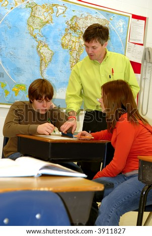 A teacher goes over lessons with teenage students in school classroom setting.