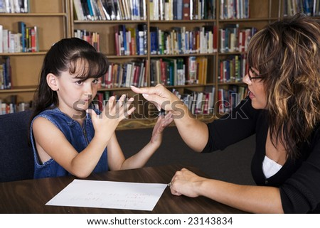 A teacher helps a child count on her fingers to figure out a math problem.