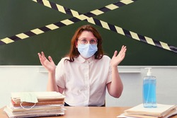 A teacher in a medical mask throws up his hands in dismay. Concept of problems with learning during coronavirus quarantine. Classroom safety during lessons in the coronavirus epidemic