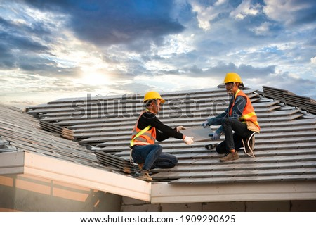 A team of Asian engineers install the new CPAC roof, roofing tools, electric drill, and use it on the new roof with the concept of building CPAC roof houses