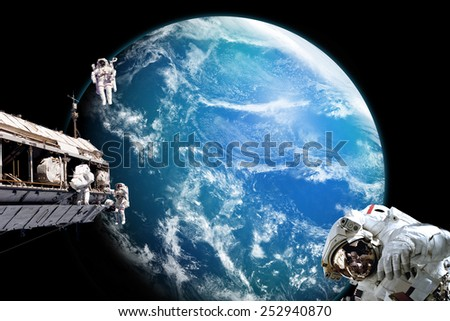 A team of astronauts perform work on a space station while orbiting above an alien water covered planet. Clouds swirl over the planet\'s ocean. -  Elements of this Image Furnished by NASA.