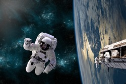 A team of astronauts perform work on a space station while orbiting Earth. The Baltic regions appear below. Elements of this Image Furnished by NASA.