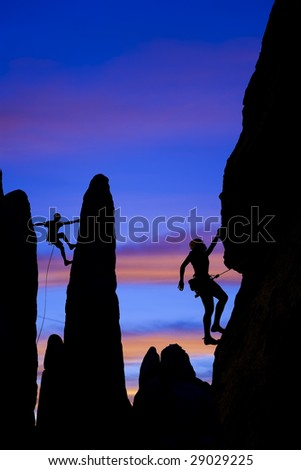 A team of climber is silhouetted against the evening sky as they ascend a steep rock face in Joshua Tree National Park, California.