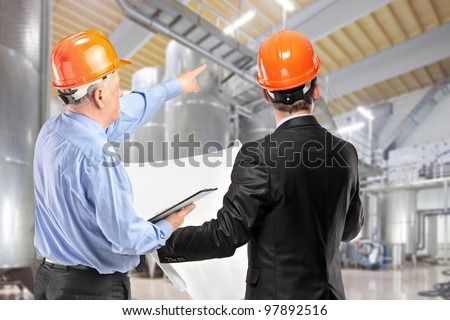 A team of construction workers with orange helmets at work place in a factory