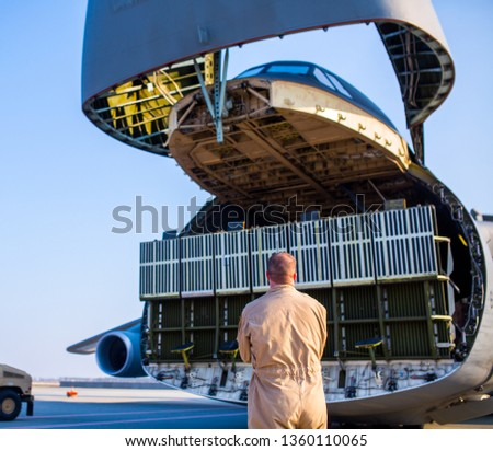 A team of engineers, US Air Force troops serve a cargo aircraft. This is not the airshow.