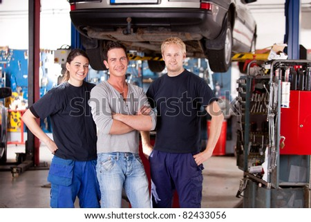 A team of mechanics in a shop with a car on a hoist