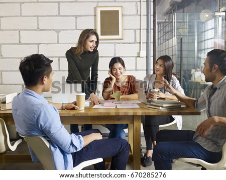 a team of multinational people discussing business in glass meeting room.