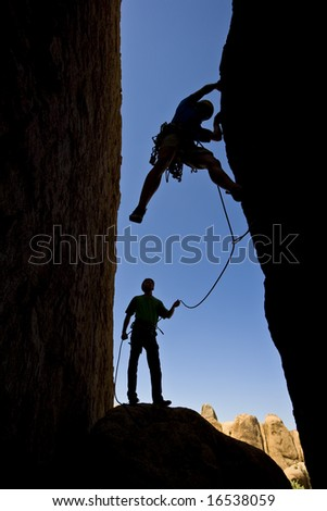 A team of rock climbers are silhouetted as they work their way up a chimney in Joshua Tree National Park.