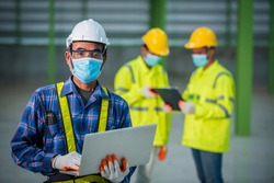 A team of three Asian construction engineers and architects joined forces to wear a Corona virus or Covid-19 protective mask during construction design at the construction site.